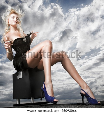 Beautiful girl sitting against cloudy sky - stock photo