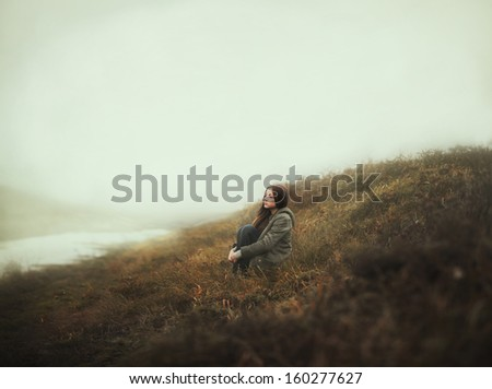 beautiful girl sitting alone autumn morning - stock photo