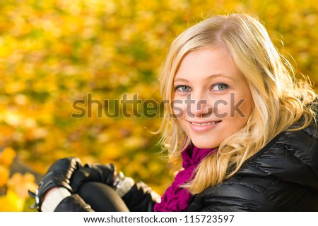 Beautiful girl sitting, autumn color leaves on the background, horizon format - stock photo