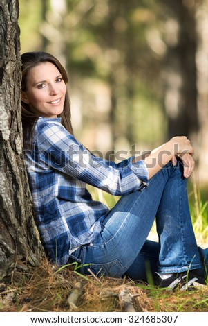 Beautiful girl sitting by pine tree - stock photo