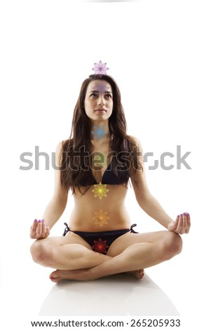 Beautiful girl sitting in lotus position with seven chakras isolated on white background. Consciousness, enlightenment and yoga. - stock photo