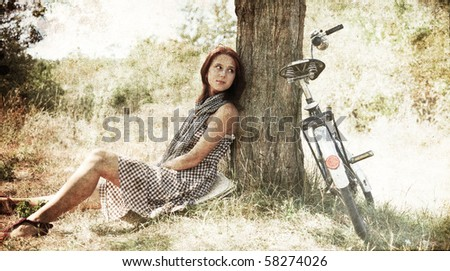 Beautiful girl sitting near bike and tree at rest in forest. Photo in old colour image style. - stock photo