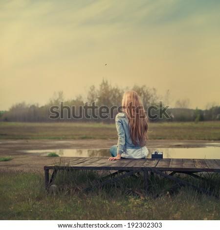 beautiful girl sitting near the old camera - stock photo