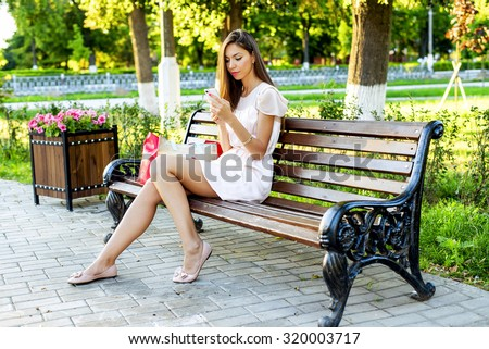 Beautiful girl sitting on a bench, brunette in a pink dress, fashion life style with your phone writes a message on social networks, sunny day in the park, relaxing, after work business woman. - stock photo