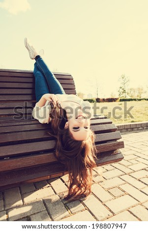 beautiful girl sitting on a bench, outdoor lifestyle portrait - stock photo