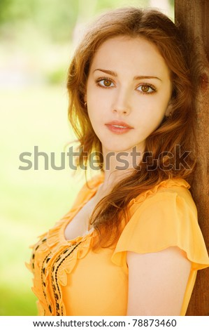 beautiful girl sitting on a park bench leaning on wooden wall - stock photo
