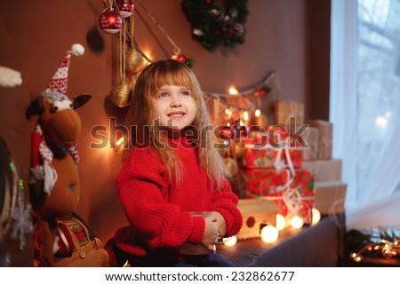 beautiful girl sitting on a sofa. New Year. Christmas decorations and gifts - stock photo