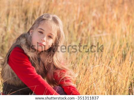 beautiful girl sitting on grass - stock photo