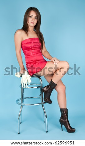 Beautiful girl sitting on the bar chair with white gloves - stock photo