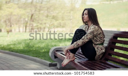 Beautiful girl sitting on the bench - stock photo