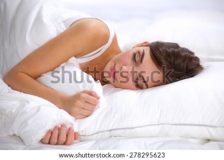 Beautiful girl sleeps in the bedroom, lying on bed. - stock photo