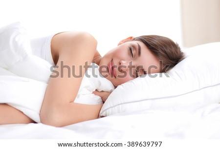 Beautiful girl sleeps in the bedroom, lying on bed - stock photo
