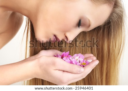Beautiful girl smelling the flower petals in spa - stock photo