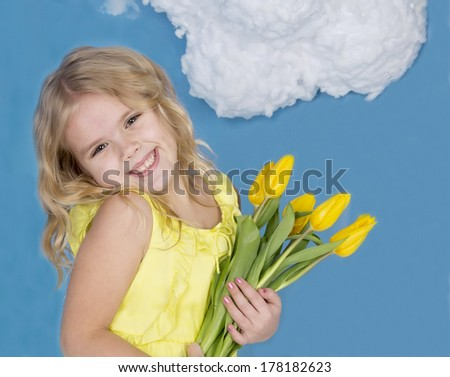 beautiful girl smiling and holding a bouquet of yellow tyupanov - stock photo