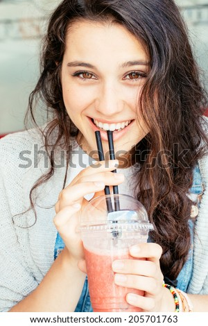 Beautiful girl smiling drinking a fruit smoothie outdoors - stock photo