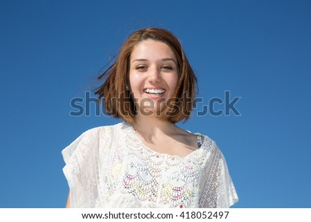 Beautiful girl smiling on the blue sky - stock photo