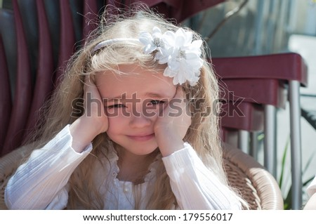 Beautiful girl squinting in the sun - stock photo