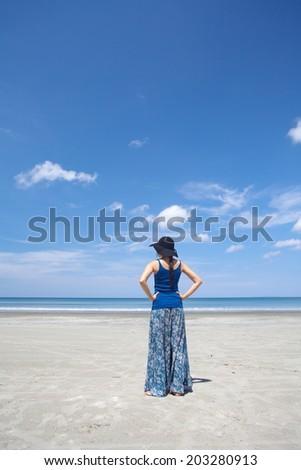 Beautiful girl standing at beach - stock photo