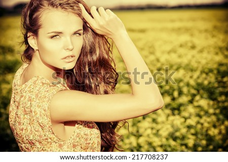 Beautiful girl standing in a field of blooming yellow flowers. Summer. - stock photo