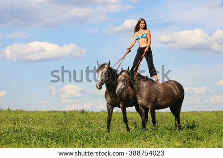 Beautiful girl standing on two horses - stock photo