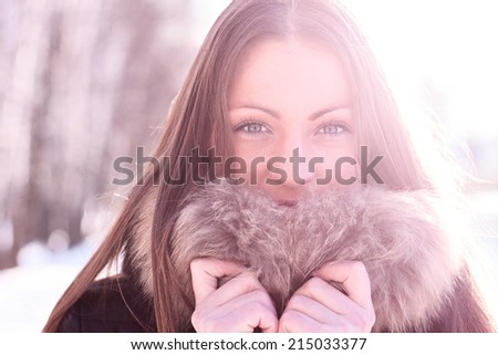 Beautiful girl standing outdoors in winter - stock photo