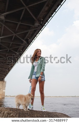 beautiful girl standing  with little cute dog  - stock photo