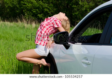 Beautiful girl stands near to white car - stock photo