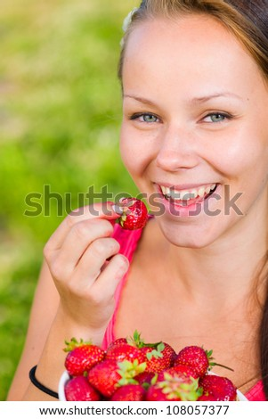 Beautiful girl taste a strawberry,  full bowl of berries, focus on the eyes - stock photo