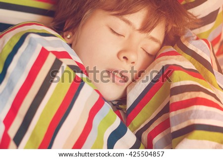 Beautiful girl teenager asleep in bed under a striped colored blanket. Toned - stock photo