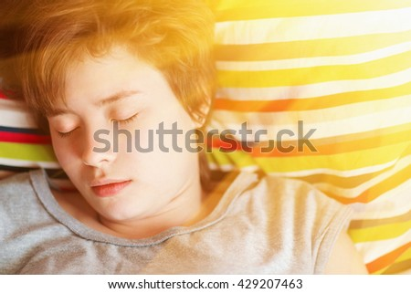 Beautiful girl teenager in the gray pajamas asleep in bed on colored striped pillow, sunny. Toned - stock photo