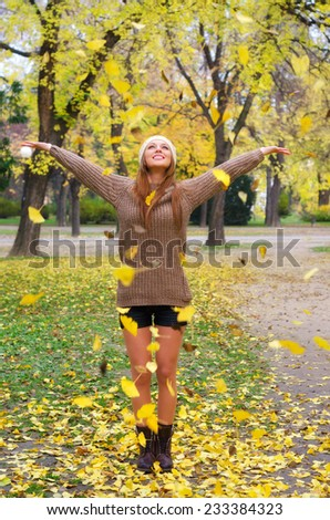 Beautiful girl throwing leaves in the air in autumn forest. - stock photo