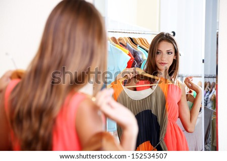 Beautiful girl trying dress near mirror on room background - stock photo