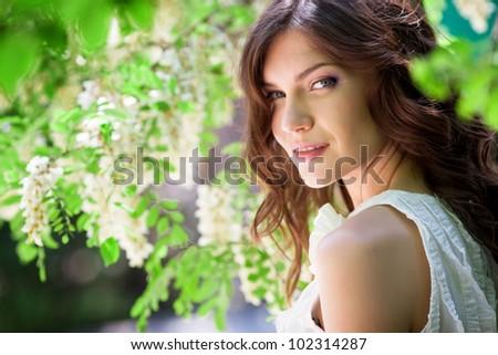 Beautiful girl under blossom acacia tree - stock photo
