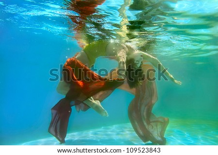 Beautiful girl under water with a long red fabric - stock photo