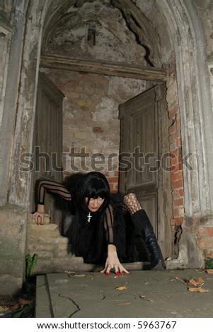 beautiful girl vampire in the old crypt - stock photo