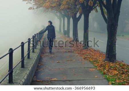 Beautiful girl walking alone on pedestrian walkway beside river on misty autumn day. - stock photo