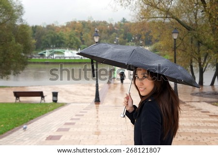 Beautiful girl walking in a park, looking back while holding umbrella - stock photo