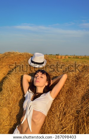 Beautiful girl was tired and lay down in the hay - stock photo