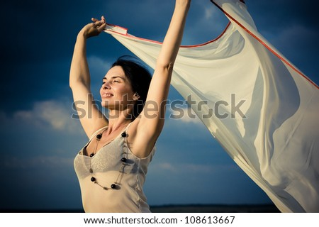 Beautiful girl waving white scarf on the background of magnificent blue sky - stock photo