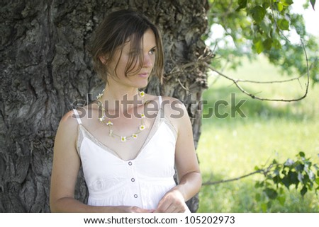 Beautiful girl wearing a daisy chain necklace in the countryside - stock photo
