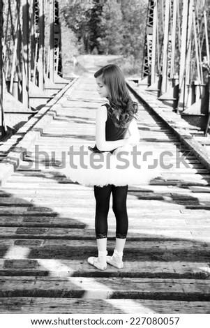 Beautiful girl wearing a white tutu standing on a bridge  - stock photo