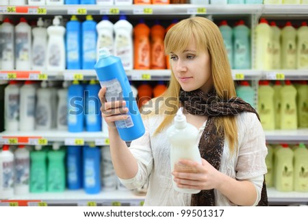 Beautiful girl wearing scarf compares abstergents in shop; shallow depth of field - stock photo