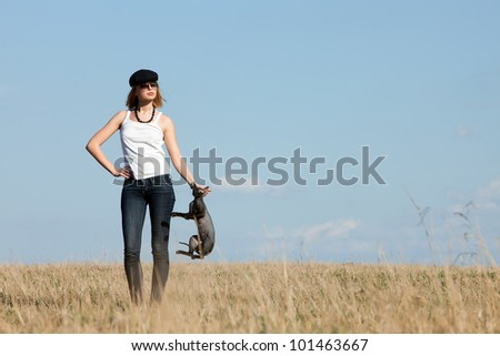 beautiful girl with a bald black cat in his hands against the blue sky - stock photo