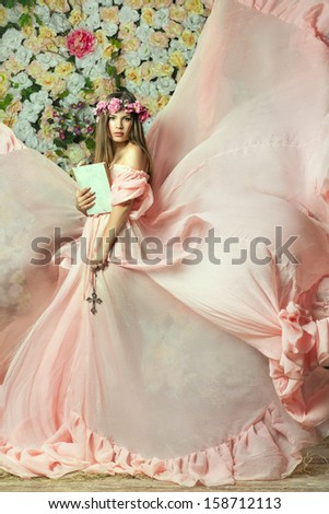 beautiful girl with a book and a cross in his hand. - stock photo
