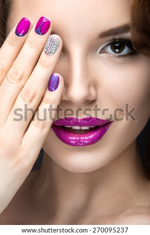 Beautiful girl with a bright evening make-up and purple manicure with rhinestones. Nail design. Beauty face. Picture taken in the studio on a black background. - stock photo