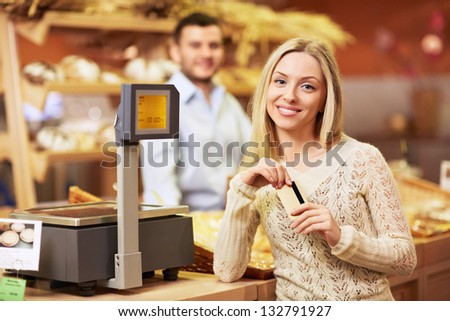 Beautiful girl with a credit card in a store - stock photo