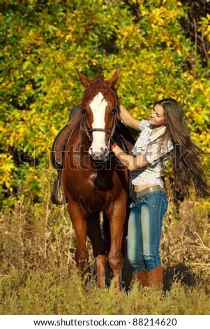 Beautiful girl with a horse  in countryside. - stock photo