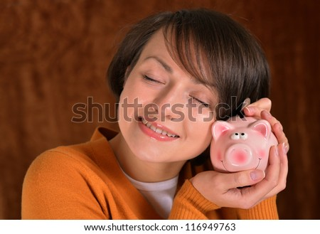beautiful girl with a piggy bank on a brown background - stock photo