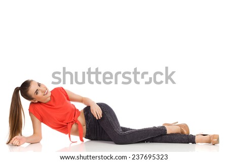 Beautiful girl with a ponytail. Smiling girl with in red top, black jeans and high heels lying on the floor. Full length studio shot isolated on white. - stock photo