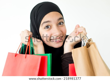 Beautiful girl with a scarf in shopping holding bags - stock photo